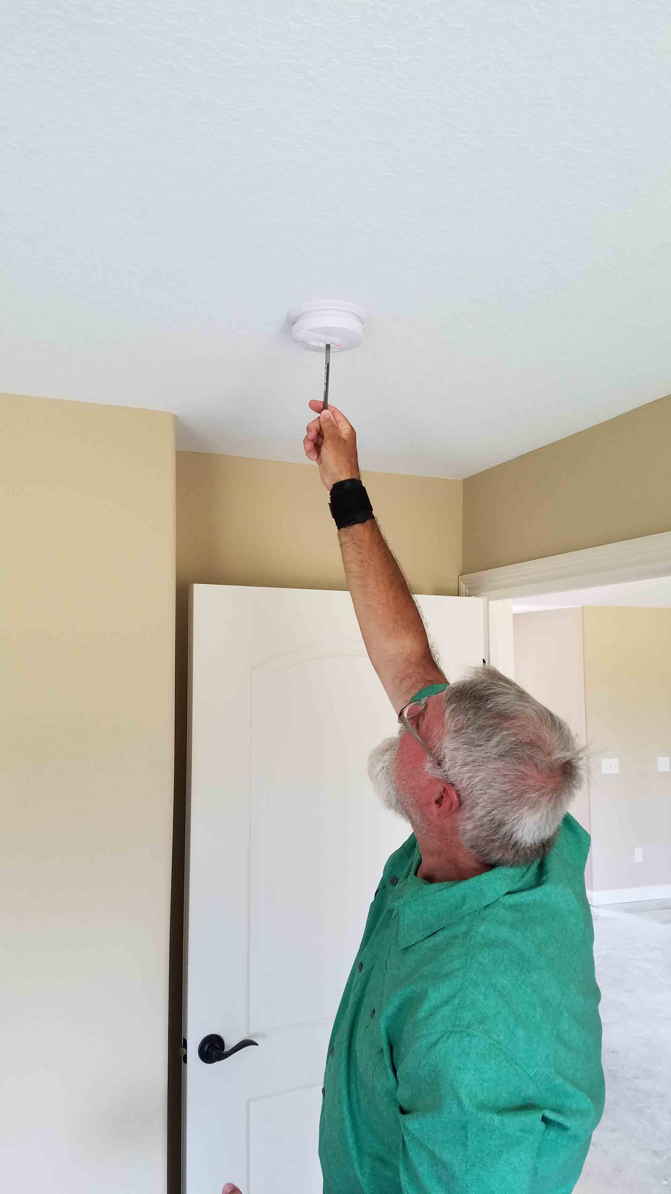 Building Commissioner Testing Smoke Alarm