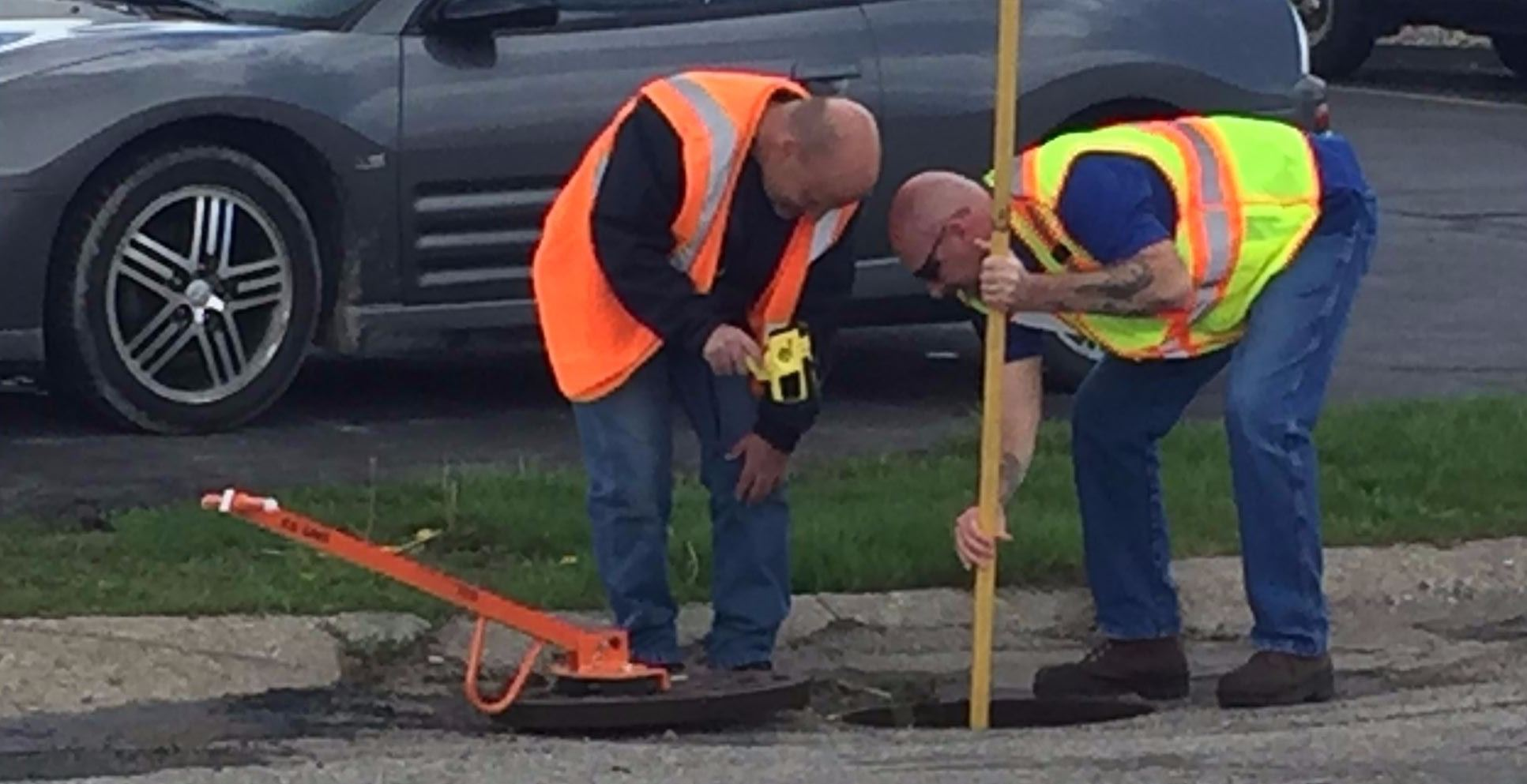 Employees checking manhole